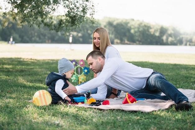 봄 날에 공원에서 잔디에 앉아 행복한 가족