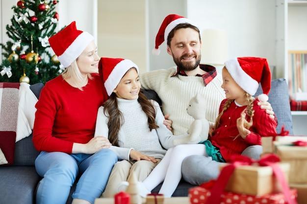 ソファに座ってクリスマスプレゼントを開梱する幸せな家族