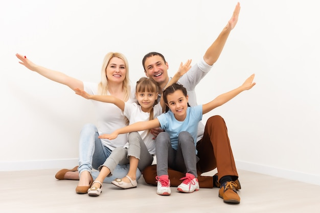 木の床に座って幸せな家族。一緒に楽しんでいる父、母と子。引っ越しの日、新しい家のコンセプト