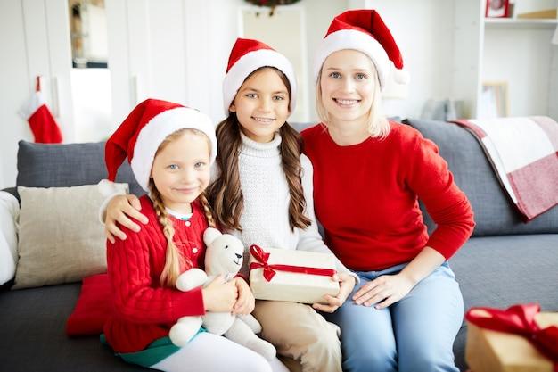 Famiglia felice che si siede sul divano e scartare i regali di natale