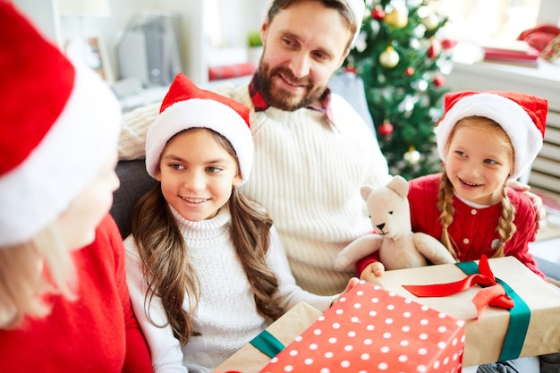 Happy family sitting on the sofa and unwrapping christmas presents