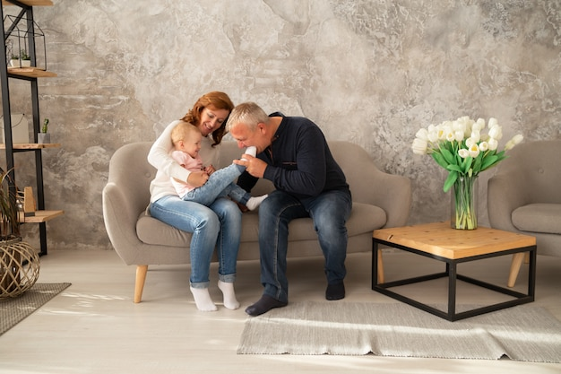 Happy family sitting on the sofa with baby girl. grandfather and grandmother spend their day together with granddaughter indoor