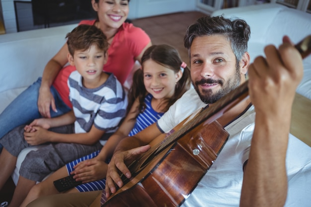 Happy family sitting on sofa with a guitar