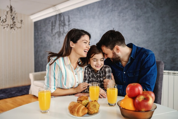 Happy family sitting together at dining table in the morning. mom and dad cuddling their only child.