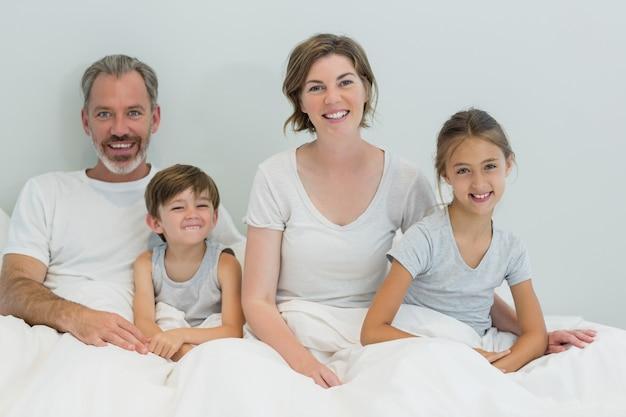 自宅の寝室のベッドに一緒に座って幸せな家族