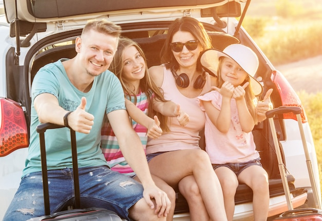 Happy family sitting on a trunk of a car with on a travel vacation