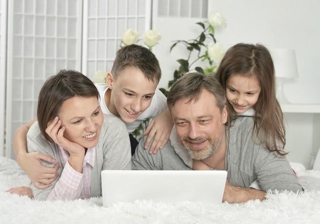 家でラップトップと一緒に座っている幸せな家族