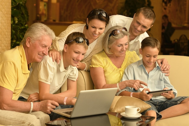 テーブルの上にラップトップと座って幸せな家族
