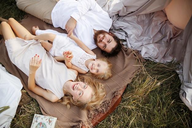 幸せな家族は笑顔で草の上にあります。夏のピクニック