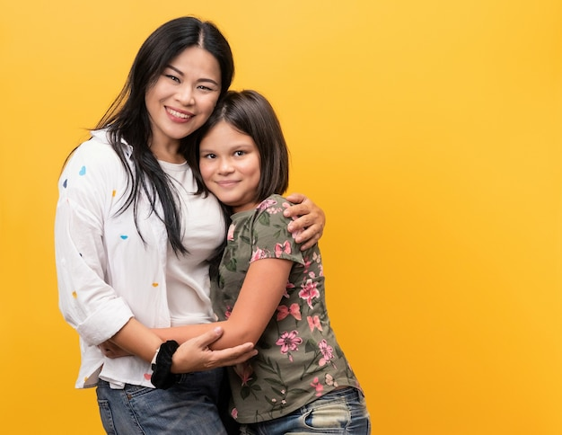 Happy family, smiling mom with her daughter. young woman and teen girl dressed in casual clothes poses embracing