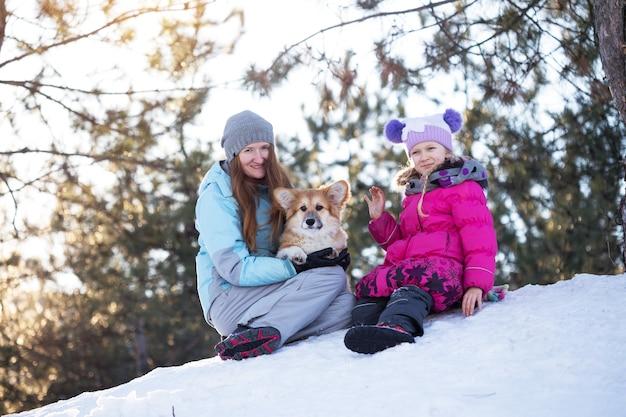 Счастливая семья - улыбающиеся мать и дочь с маленьким милым пушистым щенком корги в зимний день