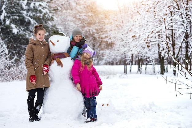Счастливая семья - улыбающаяся мать и дочери со снеговиком в зимний день