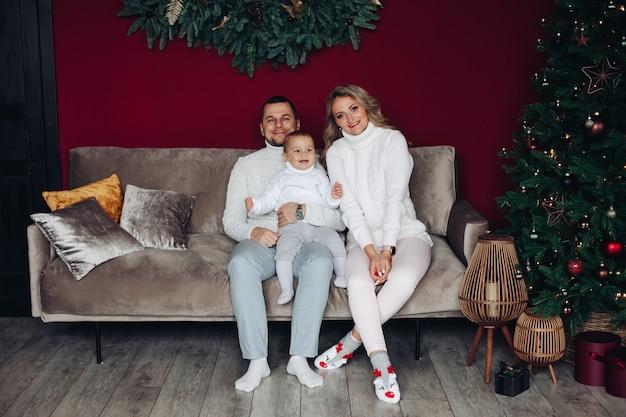 Famiglia felice sul divano a natale.