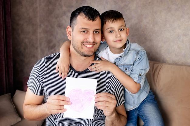 행복한 가족, 아들은 아버지에게 크리스마스 카드를 제공합니다.