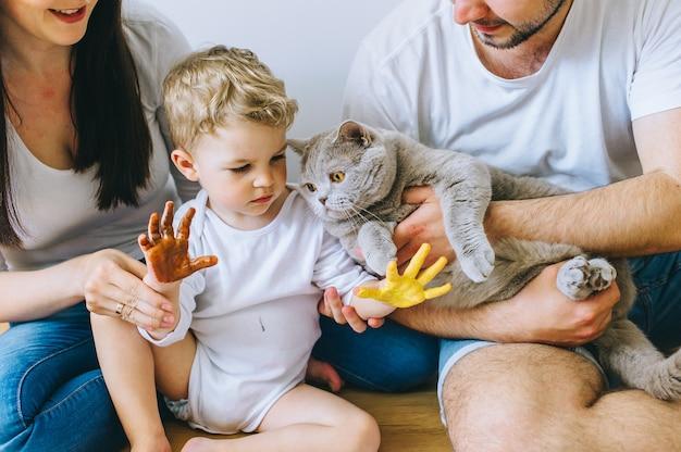 両親と猫と幸せな家族の息子、ポスターを描く