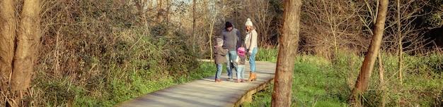 森への木製の小道で一緒に話したり遊んだりする幸せな家族