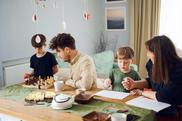 幸せな家族は家で一緒に時間を過ごし、父は息子とチェスをし、母は家で子供と一緒に絵を描く