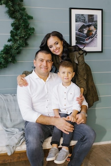 幸せな家族はクリスマスに一緒に時間を過ごします。冬休みのお母さんのお父さんと息子の肖像画