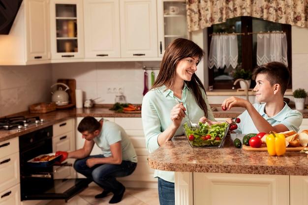 食糧を準備するキッチンで時間を過ごす幸せな家族