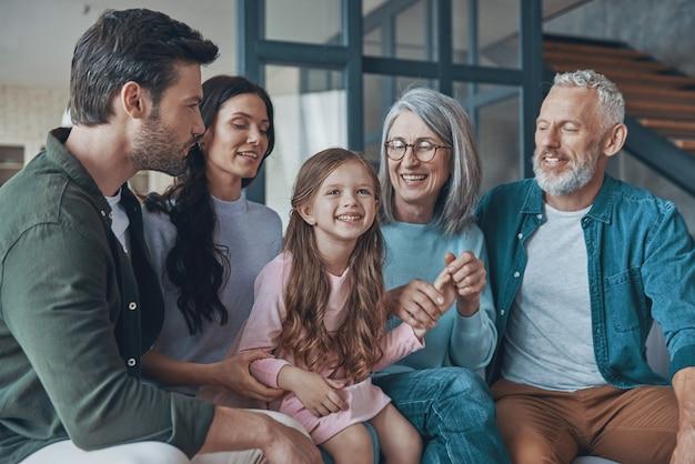 Счастливая семья, проводя время вместе и улыбаясь, сидя на диване у себя дома