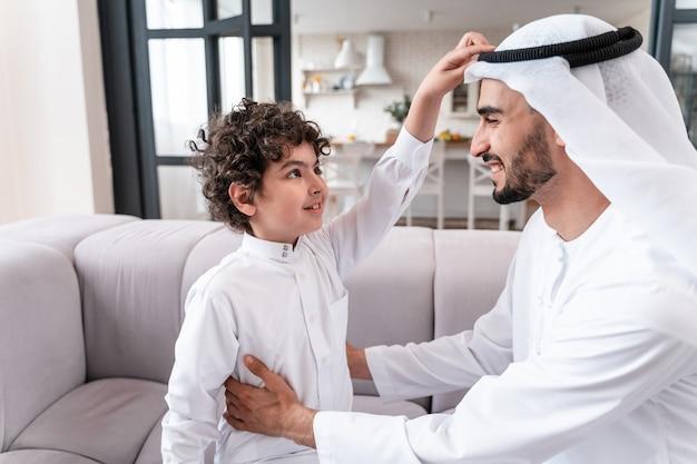 함께 시간을 보내는 행복한 가족. 아라비아 아버지와 그의 아들이 학교에 갈 준비를 하고 있다