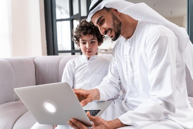 함께 시간을 보내는 행복한 가족. 컴퓨터에서 함께 공부하는 아라비아 아버지와 그의 아들
