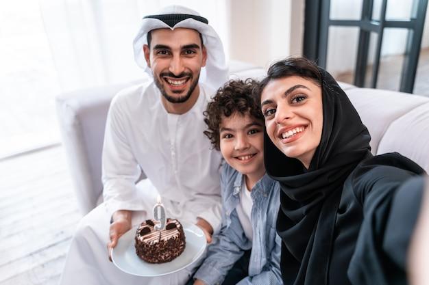 행복한 가족이 함께 시간을 보내는 아라비아 부모와 아이가 함께 생일을 축하합니다