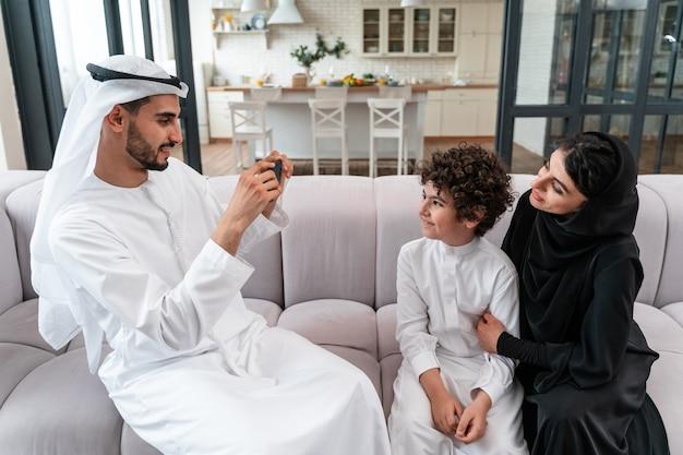 함께 시간을 보내는 행복한 가족. 아라비아 부모와 그들의 아들이 집에서 놀고 다양한 활동을 한다