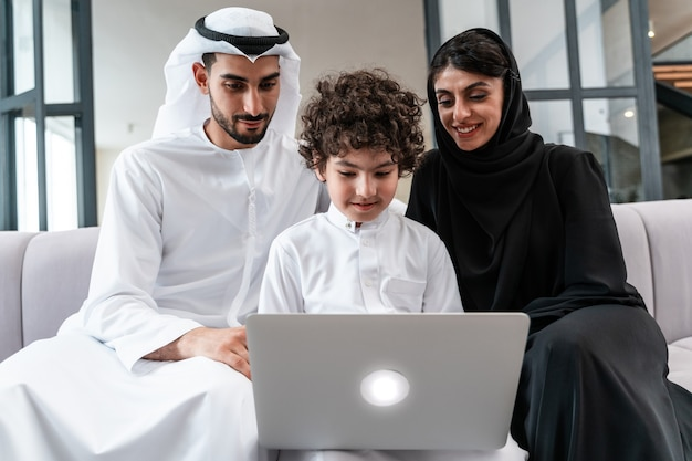 Happy family spending time together. arabian parents and their son playing and making different activities at home