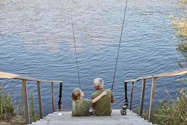 川や湖の近くの戸外で一緒に時間を過ごす幸せな家族、息子は水に通じる木製の階段に座っている間彼の父を愛で抱き締めます。