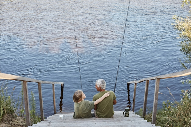 Happy family spending time together in open air near river or lake, son hugging his father with love while sitting on wooden stairs leading to water.