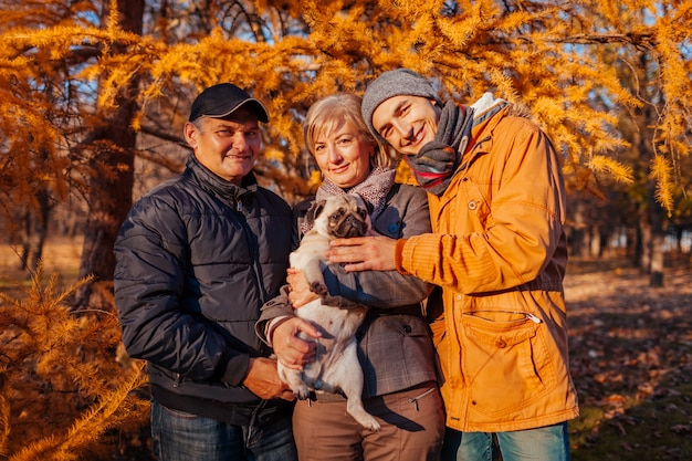 Happy family spending time with pug dog in autumn park parents with their son hugging pet