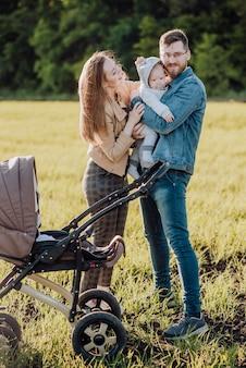 幸せな家族は屋外で時間を費やしています。母親と父親は腕の中で赤ちゃんを保持します