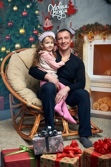 Happy family spends time together on winter vacation at home by the fireplace near the christmas tree with gifts. cute little girl with her father in the chair at the christmas tree.