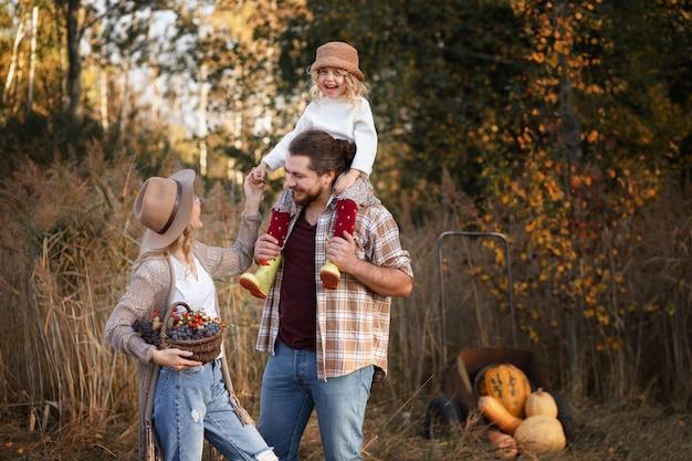 カボチャの束の隣に立っている幸せな家族