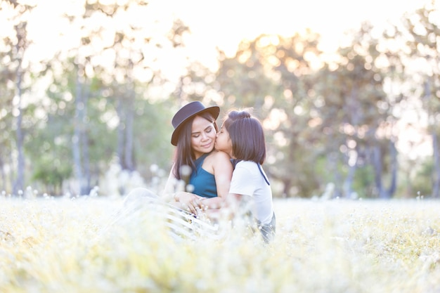 Happy family on a summer meadow, portrait of little girl giving kiss to her mom on mother's day