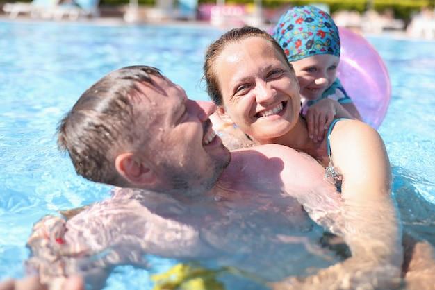 幸せな家族がプールで泳ぎます。
