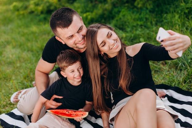 행복 한 가족 공원 근접 촬영에서 피크닉 중 사진 selfie를 가져가 라.