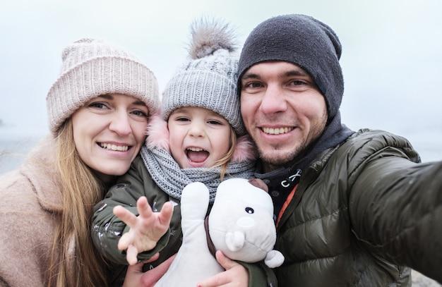 Счастливая семья делает селфи - родители и ребенок фотографируют себя на телефон