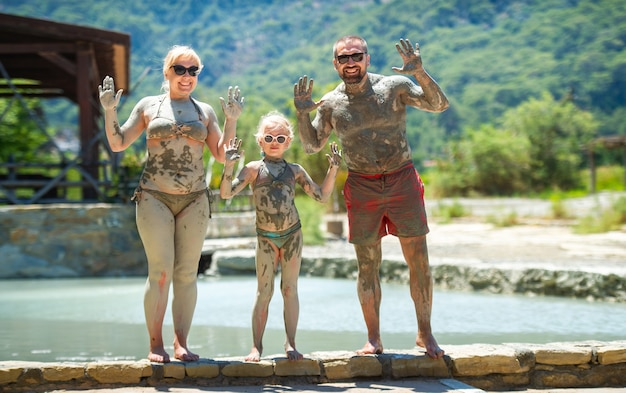 A happy family takes a mud bath at a resort in turkey.family wellness in therapeutic mud