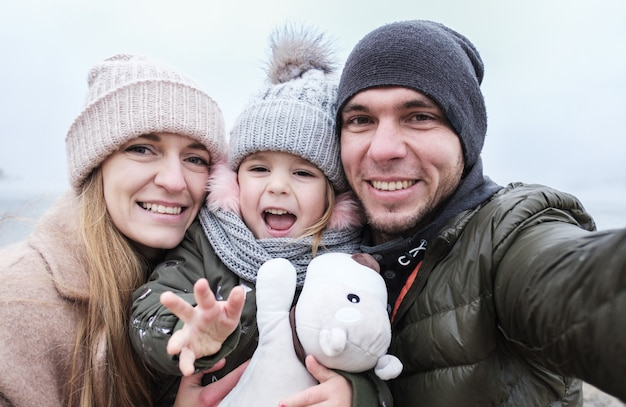 Happy family takes a selfie - parents and child take pictures of themselves on the phone