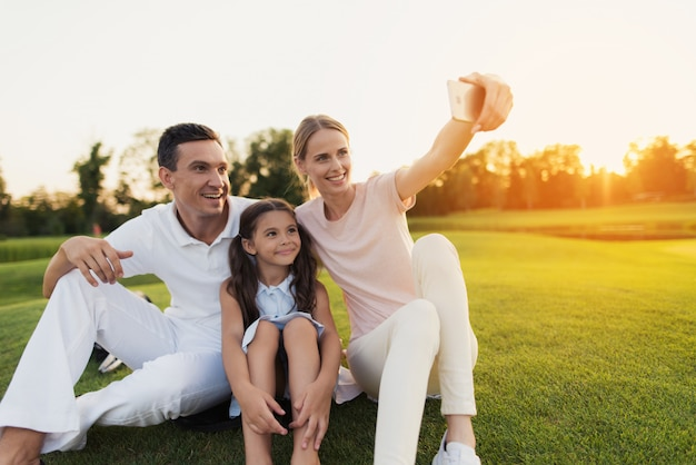Happy family takes selfie sitting on green lawn.