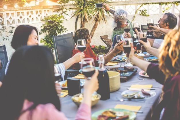 家の裏庭でのバーベキューディナーでスマートフォンカメラでselfie写真を撮る幸せな家族
