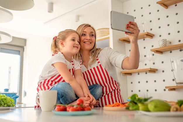 料理をしながら一緒に自分撮りをする幸せな家族