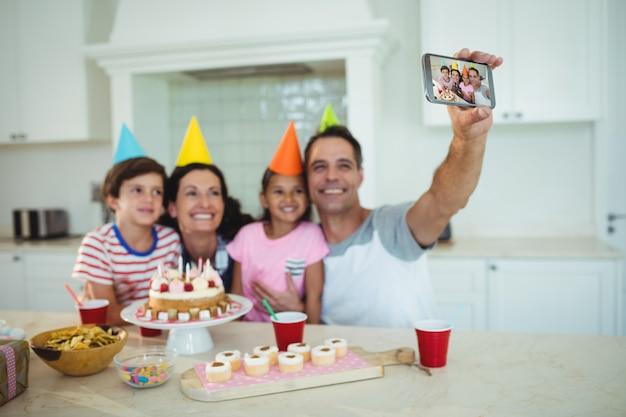 誕生日を祝っている間、幸せな家族が自分撮りをして
