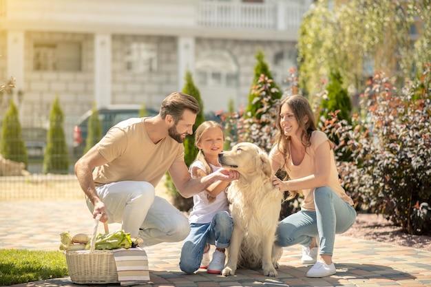 Счастливая семья гуляет вместе со своей собакой