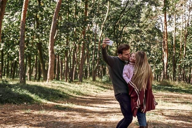 Счастливая семья, делающая селфи с помощью смартфона в лесу. отец держит смартфон с камерой