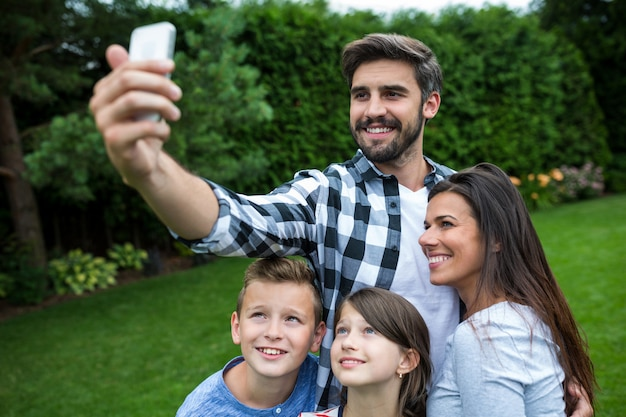 Happy family taking a selfie from mobile phone in park