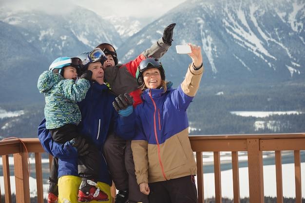 携帯電話で自分撮りをしている幸せな家族