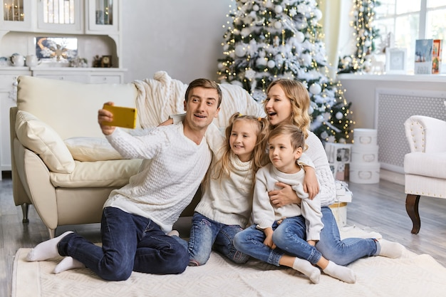 自宅でスマートフォンで自分撮り写真を撮る幸せな家族